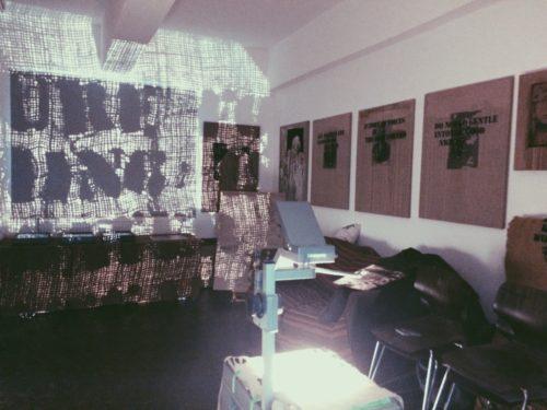 Ausstellungsansicht eines Raumes mit Prrojektionen an den Wänden. Sie überlagern teilweise Gemälde und Möbelstücke