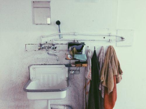 Ausstellungsansicht mit einem weißen Waschbecken daneben Hantücher
