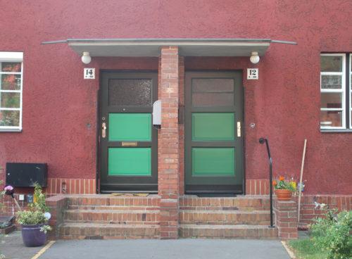 Zwei grüne Türen, die horizontal in drei Teile gegliedert sind, wobei das oberste Drittel aus Glas besteht und mit drei Stufen in ein rotes Wohnhaus führen