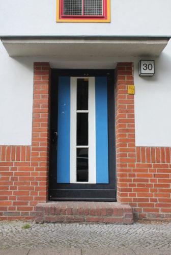 Ein hellblaue Tür mit vertikal verlaufenden Fenstern in der Mitte und einer Backsteinrahmung, die mit einer Stufe in ein Wohnhaus führt