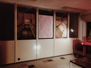 Ausstellungsansicht mit großformatigen Fotografien vor den Fensterscheiben