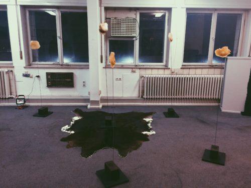 Ausstellungsansicht mit einem Fell auf dem Boden und schlanken Skulpturen die im Raum vor einer Fensterfront verteilt sind