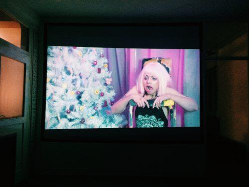 Filmstill das eine junge Frau mit blondem Haar neben einem Weihnachtsbaum zeigt