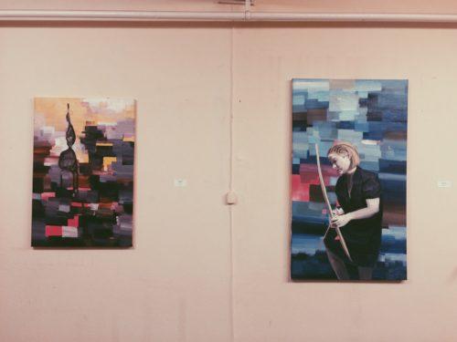 Zwei bunte Gemälde mit eckigem, grafischem Hintergrund. Auf einem ist ein Mensch im Vordergrund zu erkennen