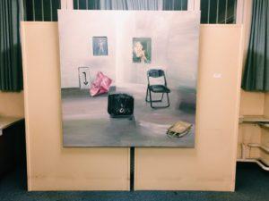 Ein Gemälde, das einen Raum mit Kunstwerken und einem Stuhl wiedergibt