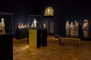 Die Abbildung zeigt den Ausstellungsraum aus einer weiteren Parespektive. Die Vitrinen der Christuskinder sind im Hintergrund erkennbar. Weitere sich im Raum  befindende Skulpturen sins erkennbar.