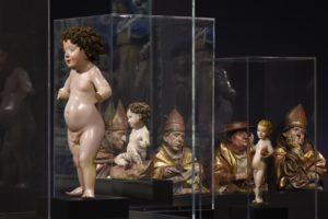 Auf der Abbildung ist der Ausstellungsraum zu sehen. Das stehende Christuskind ist auf der linken Bildseite, hinter und neben ihm sind weitere Skulpturen in Vitrinen zu sehen.
