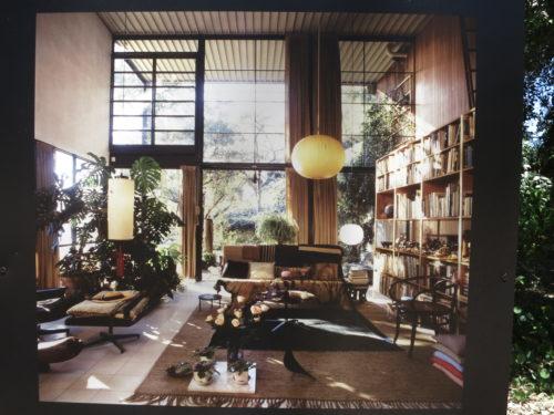 Abgebildet ist der Innenraum eines Hauses. Das Wohnzimmer ist groß und lichtdurchflutet, mit bodenlangen Fenstern.Auf der rechten Seite ist ein großes Bücherregal, daneben der mittigen Couch und dem Couchtisch steht. Es hängen meghrere Runde und ovale Lampen von der Decke.