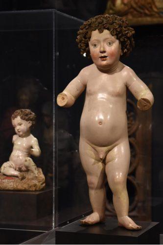 Abgebildet ist ein stehendes, nacktes Christuskind im Vordergrund. Links im Hintergrund ist ein sitzendes, ebenfalls nacktes Christuskind zu sehen. Beide Skulpturen sind aus Holz aber fast vollständig farbig gefasst. Dem stehenden Kind fehlen beide Unterarme. Es hat dunkle Locken und ein rundes Gesicht.