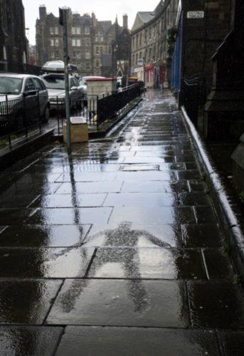 Filmstill einer menschenförmigen, trokenen Fläche auf einem regennassen Gehweg