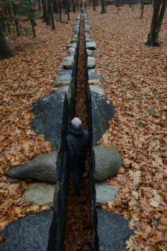 Filmstill wie der Künstler durch einen schmalen Weg im Wald läuft, der mit großen Steinen ausgekleidet ist und wie ein kerzengerader Einschnitt in Wand wirkt