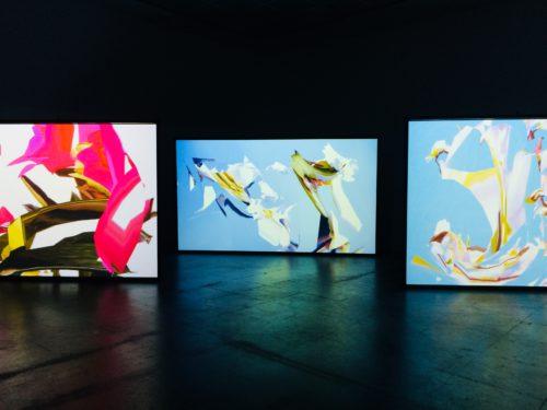 Drei hinter- und nebeneinander gestaffelte große Projektionen die computergenerierte Muster zeigen in den Farben Hellblau, Weiß, Gelb und Pink