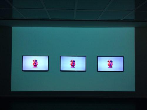 Videoinstallation auf drei nebeneinander angebrachten Bildschirmen die ein computergeneriertes Gesicht zeigen