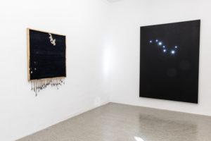 Ausstellungsansicht zweier Kunstwerke, die beide sehr dunkel gehalten sind. Links ein Werk aus Stoff und Fäden, rechts eine schwarze Leinwand mit kleinen Lichtern die ein Sternbild nachbilden