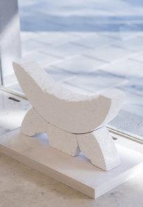 Eine Skulptur aus weißem, porösem Stein in der Form eines nach oben gerichteten Halbmondes der auf drein Stüzen ruht