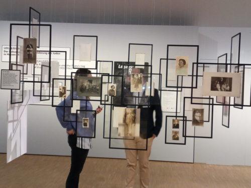 Ausstellungsansicht mit Rahmen und historischen Fotografien die im Raum hängen