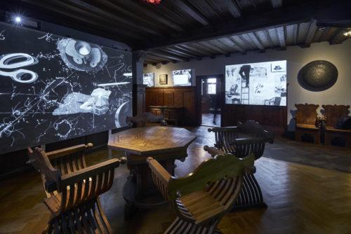 Die Räumlichkeiten des Liebieghauses mit den historischen Möbeln werden um Viedeoinstallationen des Künstlers erweitert. Hier eine Viedeoarbeit vor einem historischen Tisch mit Stühlen