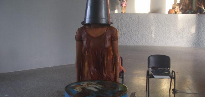 Eine schwarze Frau hat einen Metalleimer über ihren Kopf gestülpt und ist nass. Sie steht in einem Ausstellungsraum, vor ihr ein blauer Wassertank, hinter ihr ein Stuhl. Weit im Hintergrund auf einer Tribüne sieht man Zuschauer sitzen.