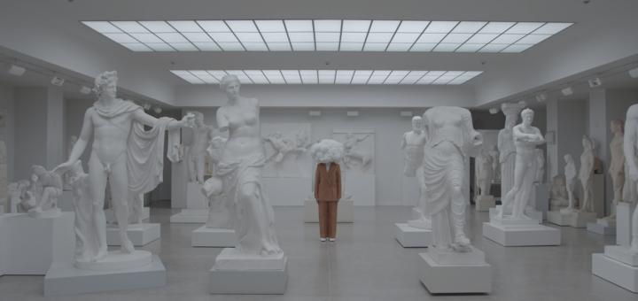 Zwischen den weißen Skulpturen sticht ein im rotbraunen Anzug gekleideter Mensch mit einer Wolke auf den Schultern, der Cloudy Mind, anstelle eines Kopfes hervor. Die Person verweilt zwischen den Figuren in einem Raum der von Oberlichtern beleuchtet wird.