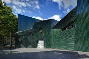 Die Fotografie zeigt den Fronteingang der neuen Synagoge. Gut zu erkennen ist die gerippte Oberfläche der Fassade und ihr grünlicher Schimmer.