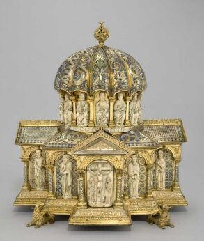 Zu sehen ist ein Turmreliquiar aus vergoldetem Silber und Bronze, Gold und Elfenbein. Die Form erinnert an eine Kirchenarchitektur, mit einer Kuppel. Das Reliquien steht auf vier vergoldeten Füßchen.,