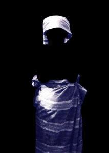 Vor einem schwarzen Hintergrund erkennt man lilane Gewänder und ein Kopftuch. Die Formen zeigen, dass sie von einer Frau getragen werden aber man sieht die Frau nicht. Sie ist vor dem Hintergrund verschwunden