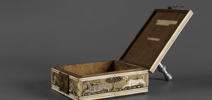 Die Fotografie zeigt ein geöffnetes Minnekästchen, welches an den Seiten verziert ist, aber einen ungeschmückten, leeren Innenraum offenbart.