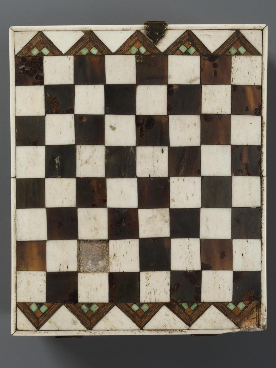 Die Unterseite des Minnekästchens ist mit einem Schachbrettmuster verziert. Die hellen Felder aus Knochen  oder Elfenbein, die dunklen aus Holz.