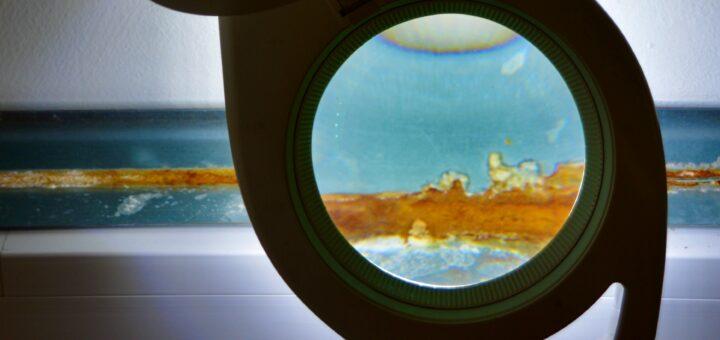 Die Fotografie zeigt ein vergörßerungsglas, welches auf eine horizontal im Bild veralufende, blau und gelb gemusterte Fläche gerichtet ist. Dort, wo man durch das Vergrößerungsglas hinschaut, ist die Fläche erhellt. Um es herum, ist es abgedunkelt.