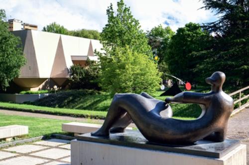 Das Aufnahme zeigt eine liegende Bronzeskulptur. die  Körperkonturen der Frau sind sehr rund und fließend, ohne kantige Ecken. Ihr Kopf ist im Gegensatz zu dem voluminösen Körper sehr kleinen und haarlos. . Die Skulptur liegt auf einem Sockel in einer Parkanlage. Im Hintergrund ist ein Gebäude zu sehen.