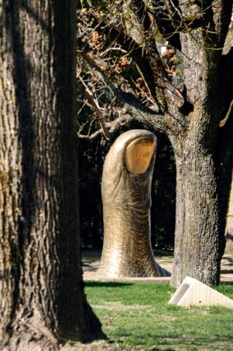 Das Bild zeigt einen großen, aus dem Boden ragenden Bronzedaumen mit goldenem FIngernagel. Die Skulptur wird von Bäumen umringt, die ihr farblich ähneln..