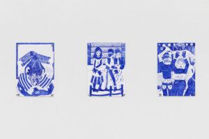 Das Foto zeigt jeweils drei Zeichnungen, die auf einer weißen Wand aufgehängt sind. Alle drei sind mit einem Lamifüller erstellt worden, wesewegen die Farbigkeit von einem deutlichen Blau geprägt ist. Die Zeichnung zur äßeren Linken zeigt eine Figur, die in sich verknotet ist. Eine Sprechblase befindet sich hier in der unteren rechten Ecke. Das mittige Bild zeigt drei Figuren vor einem Bücherschrank, in dem jedes Buch den Titel Hass trägt. Vor den Figuren ist nichmals ein Zaun aufgemalt, welches nochmal deutlicher macht, dass der Zugang hier versperrt ist, oder zumindest nicht jedem gewährt. Ganz rechts ist eine Zeichnung einer Situation. Ein Polizist mit heruntergelassener Hose und mit dem Rücken zu den Betrachter*innen ist gerade dabei auf einen Menschen einziprügeln. Eine weitere Figur steht mit ihrem Gesicht zu uns, schaut jedoch asu dem linken Bildrand heraus. Sie hat die Hände hoch genommen. Alle drei Zeichnungen haben etwas stark comic-artiges.