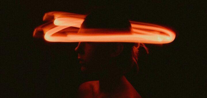 Das Bild zeigt den Kopf einer Frau. Das Bild ist sehr dunkel, nur ihr Kopf ist von einem roten Lichtkreis, ähnlich einem Heiligenschein, erhellt.