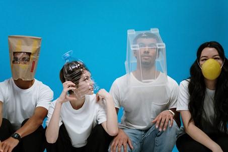 Die Fotografie zeigt vier Personen vor einem blauen Hintergrund. Alle vier sitzen in der Hocke frontal zum Betrachter und tragen verschiedene Kopfbedeckungen, wie z. B. eine Papiertüte, eine Plastikschale, einen  Plastikkasten und einen Mundschutz..