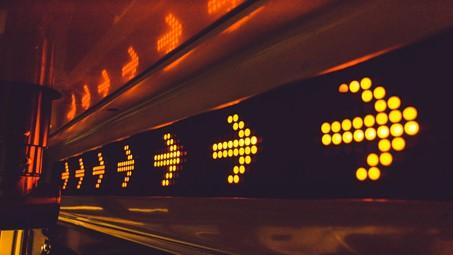 Das Bild zeigt ein Leuchtschild, auf dem sich sieben nach rechts zeigende Pfeile befinden, die durch vereinzelt Lichtpunkte ihre Pfeilform bekommen.