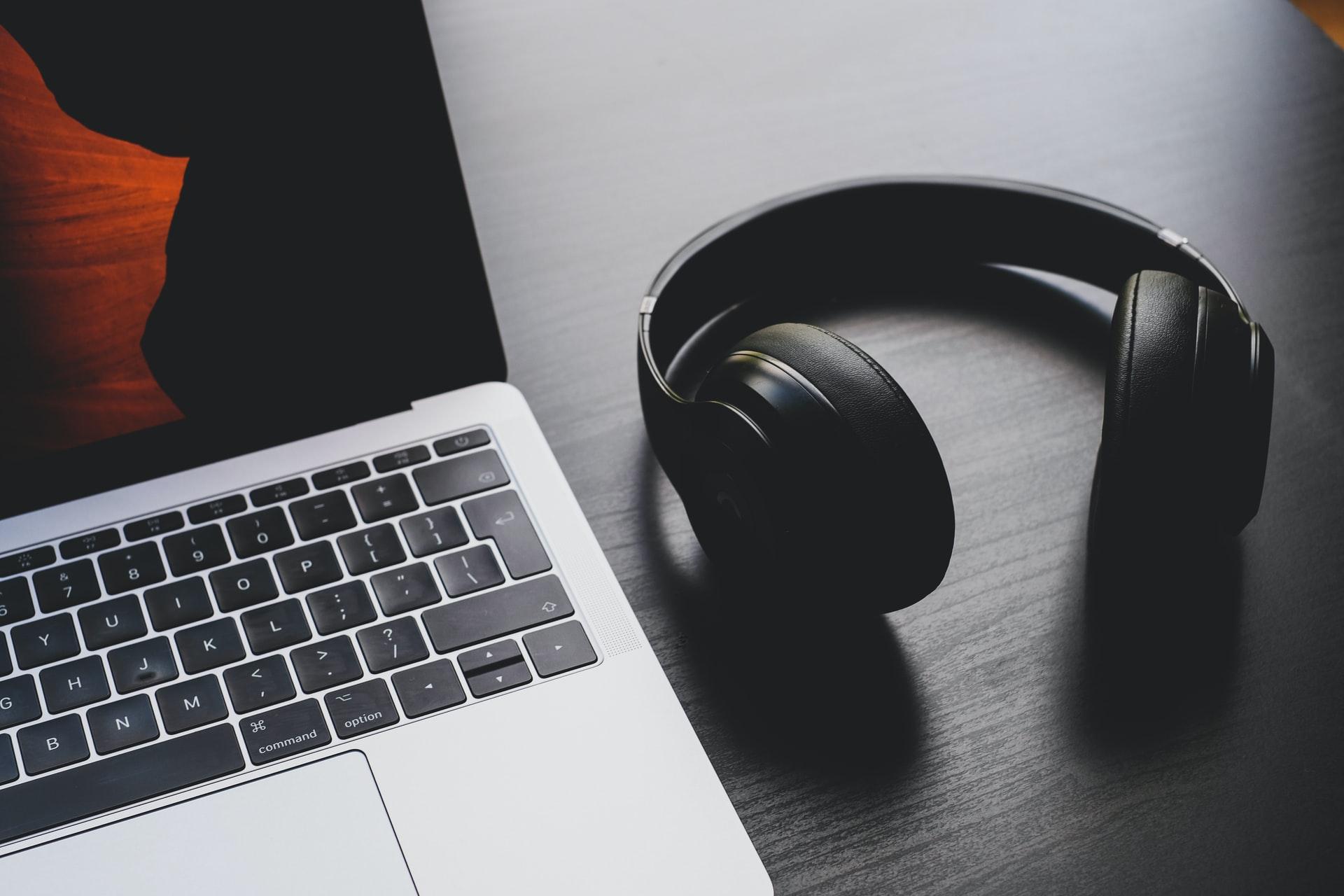 Ein Headset liegt neben einem Laptop.