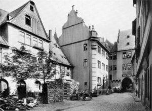 Historische Aufnahme des Nürnberger Hofes um 1897. Das Foto zeigt mehrere Gebäude in einer leicht schrägen Ansicht, hinten ist ein Torbogen zu erkennen, bei dem es sich wahrscheinlich um den südliche handelt.
