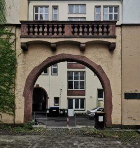 Frontale Aufnahme des nördlichen Torbogens, in schlichter, barocker Manier gestaltet. Beiges Mauerwerk mit bräunlichem Torbogen und Balustrade.