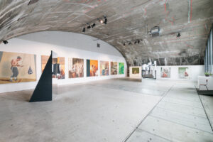 Innenraumansicht des Ausstellungsraumes mit gewölbter Betondecke und grauem Boden. Sechs gleichformatige Bilder hängen  an der linken Seitenwand. Im Raum stehen die Spiegelskulpturen. Rechts ist eine Fensterfront.