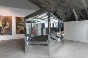 Ansicht der Spiegelskulptur im Ausstellungsraum. Eine Art kleines Haus mit verspiegelter Fassade und verspiegeltem Innenraum mit Neonröhren.