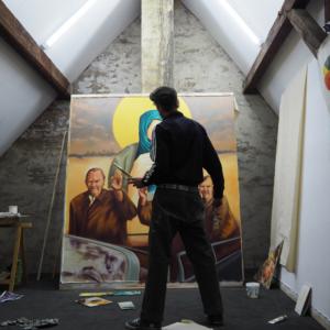 Der Maler steht mit dem Rücken zum Betrachter ganzfigurig vor einem Bild.Er hat eine Farbpalette in seiner linken Hand und schaut auf das Gemälde auf dem Personen zu erkennen sind.