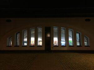 Aussenansicht des Ausstellungsortes am Abend. Vom Innenraum dringt durch die zehn länglichen Fenster Licht nach außen.