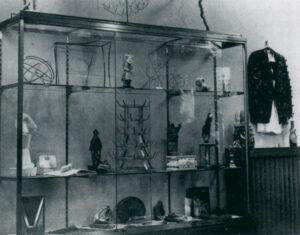 Zu Shen ist eine s/w Fotografie eines Glasschrankes, der verschiedene Readymades enthält.