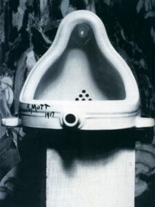 Die s/w Fotografie zeigt ein umgedrehtes Pissoir auf einem Sockel, das durch die Beleuchtung  nicht mehr an den Gebrauchsgegenstand erinnert
