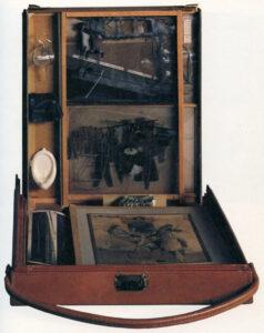 Zu sehen ist ein geöffneter, brauner kleiner Koffer, der Zeichnungen, Fotografien und Miniaturen enthält.