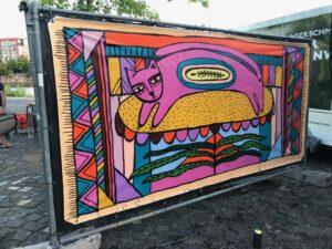 Mauerteil mit einer bunten, rosa Katze bemalt, die von farbigen Mustern und Zeichen umgeben ist.