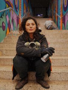Die Künstlerin sitzt auf einer Treppe an der S-Bahn-Station-Galluswarte und hält eine Spraydose in der Hand. Sie schaut in die Kamera.