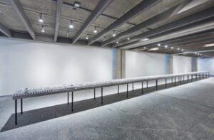 Ausstellungsansicht der auf einem langen Tisch an eine Wand entlang aufgereihten Dias.
